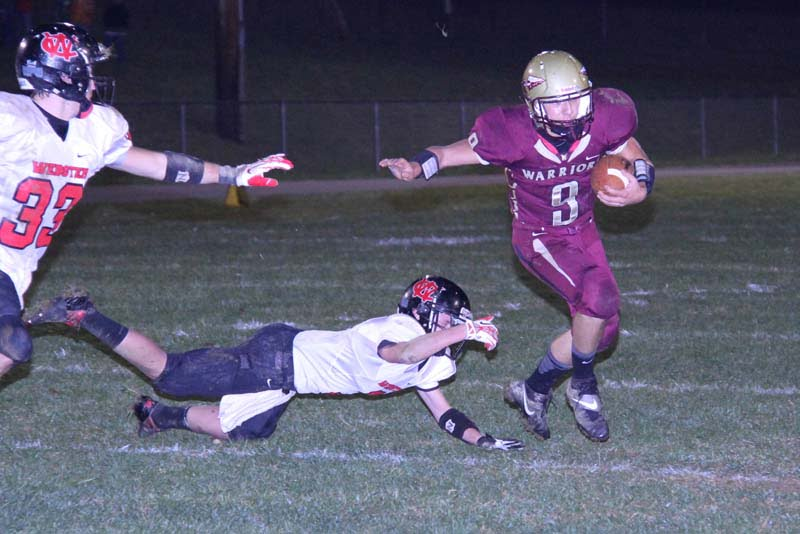 PCHS senior QB Wesley Felton avoids a tackle and scrambles for yardage against the Webster County Highlanders on November 1, 2013.