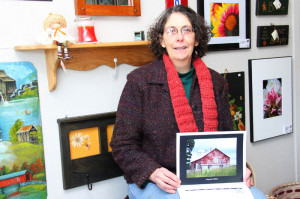 Photographer Retta Blankenship displays her 2014 calendar, which features pictures of various Pocahontas County locations adorned with quilt blocks. The calendar and a monthly planner, featuring the same photography, are available at the Fourth Avenue Gallery in Marlinton. Blankenship's artistic photography was accepted into the Artisans' Cooperative gallery last October.