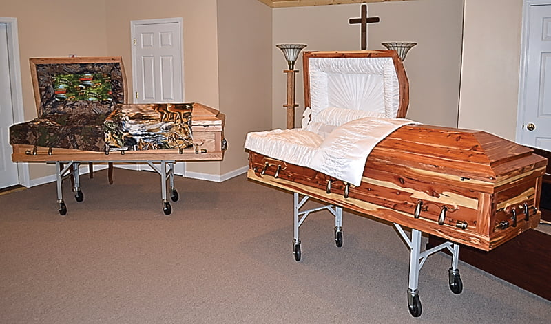 At right, Backwoods Caskets on display reveal  interior and exterior craftmanship. The camouflage-lined casket is made of oak and the other is made of cedar. S. Stewart photo