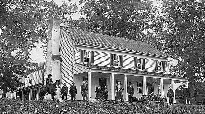 The original house on Hevener Acres in Arbovale with members of the Hevener family, in the late 1800s. On the horse, far left, is Uriah Hevener, Sr. and the child standing on the porch, sixth from left, is Uriah, Jr., grandfather of the farm's current owners Bill Hevener and his sister, Patsy Cummings. Photo courtesy of Bill Hevener