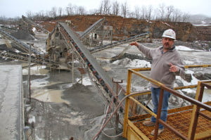 Boxley plant superintendent Howard Walker describes the rock processing facility at the company's Mill Point quarry. The company operates three crushers to produce stone as small as gravel, and plans to install a fourth to pulverize limestone gravel into agricultural lime. The new machine will be built next to the rock wall in the background and will be enclosed in a building to prevent dust from escaping the facility.