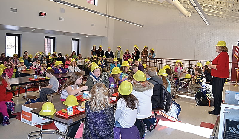 Students at Hillsboro Elementary School enjoy breakfast in the school's new cafeteria for the first time Tuesday. Students were given plastic hard hats to wear all day for the celebration. Principal Michelle Jeffers, right, greeted the students and led them in singing Happy Birthday to three students before the school day began. S. Stewart photo