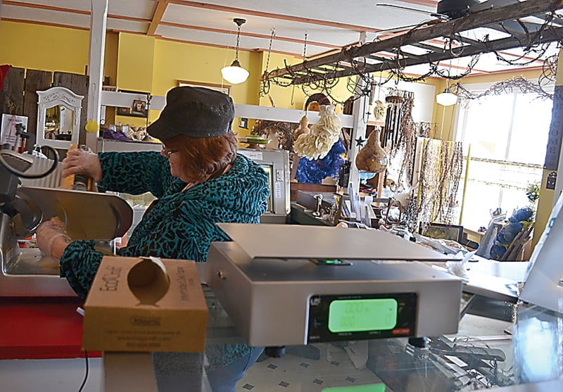 My Daughter's Attic in Hillsboro now has a deli selection offering meat, cheese, jams, jellies, chips and sweets. Above, owner Tammy Ellis slices cheese for a customer. S. Stewart photo