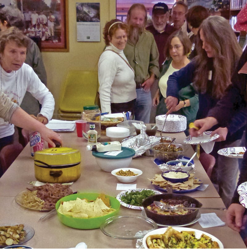 Participants in last year's Wild Edibles Festival enjoy a potluck supper at the Hillsboro Library. The festival included a field trip along the Greenbrier River Trail to search for wild edible plants and a talk by Dr. Rebecca S. Linger, assistant professor at the University of Charleston School of Pharmacy. Photo courtesy Wayne Jeffers