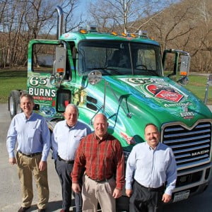 Sons and grandsons of Fred Burns, Sr., stand next to a Mack truck specially decorated to honor Burn Motor Freight's 65th anniversary. Mack Trucks paid for the graphics on two newly-purchased trucks as a gift to their long-time customer. Fred Burns, Sr., started Burns Motor Freight in 1949, when he purchased a used Mack Model LJ tractor. The company now operates a fleet of 85 trucks. In the photo, left to right: John Burns, Fred Burns, Jr. Doug Burns and Mike Burns.