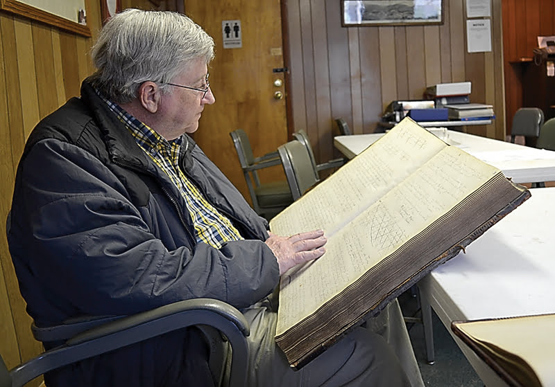 Historian Jason Bauserman peruses one of the many record books at the Durbin town office. Bauserman turned to the books to find information on the town jail and wound up finding several intriguing stories. S. Stewart photo