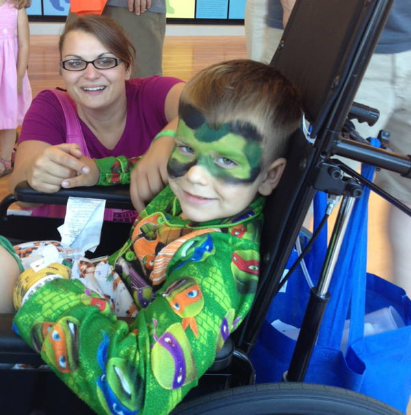 Pocahontas County native Jerry Curry VanReenen, left, with her five-year-old son,James, at the University of Virginia hospital. James spent 13 days in the hospital after he had an accident involing a lawn mower. During an open house at the hospital, James had his face painted like a Teenage Mutant Ninja Turtle. Photo courtesy of UVA Health System