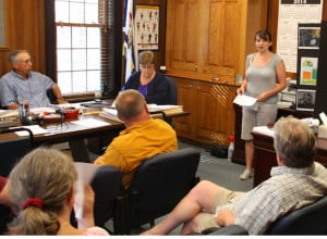 Rachel Taylor, vice president of Northern Pocahontas Wellness, standing right, speaks to the Pocahontas County Commission on June 17, 2014. Taylor requested a $10,000 contribution to help build a fitness center with an indoor pool in Green Bank.