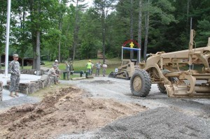 First Lieutenant Madalyn Oltman, on the left, watches as soldiers from her platoon work to improve a parking area at Buckskin Council Boy Scout Camp. The 193rd Equipment Support Platoon, from Parkersburg, conducted a training event at the camp, during which they graded roads and completed other projects.