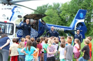HealthNet Aeromedical crew members give a safety class to school children at French Creek Elementary School on June 5, 2014. The crew had nearly completed the class when they were alerted to respond to the scene of a traffic accident in Buckhannon. Crew members, left to right: pilot Frank Figueroa, flight paramedic Carl McCormick and flight nurse Austin Browning. G. Hamill photo.