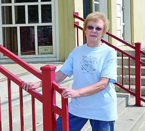 """OREANA """"RENE"""" WHITE, wearing a 4-H T-shirt and standing on the steps of the Pocahontas County Opera House.  The photo captures just two of the areas that have benefited from White's years of dedication and hard work. Pocahontas County Convention and Visitors Bureau Director Cara Rose had this to say about White: """"Over the many years I have had the privilege of knowing Rene White, many times I have passed her home and wondered how on Earth she has been able to maintain her stamina for giving so much of herself to our community."""" S. Stewart photo"""