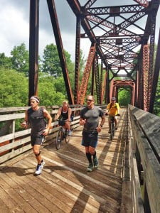 Five athletes ran and biked the entire 76-mile length of the Greenbrier River Trail on June 21 to raise funds for Payton House Hospice in Lewisburg. Donors pledged as much as $3 per mile and the Robert C. Byrd Clinic contributed an additional $500, raising a total amount of $4,104. The group started the 18-hour trek at Cass at 5 a.m. and arrived at Caldwell at 11 p.m. Completing the trip were Jim Moore, Heather Ratliff, and Tom Greenstreet, all of Lewisburg; Rick Moore, of Parkersburg, and James Towey, of Richmond, Virginia. Providing support were Monica Moore and Jennifer Cornelius, of Lewisburg. Pictured crossing Knapps Creek, left to right: Jim Moore, Monica Moore, Towey and Greenstreet. Photo courtesy Monica Moore.