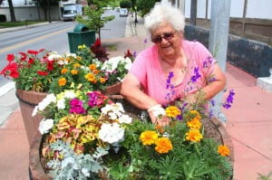 """Marlinton Councilwoman Louise Barnisky tends to flowers in large containers on Main Street in Marlinton. Barnisky started caring for the flowers after the passing of Zendik Farm owner Arol Wulfing, whose workers took care of the flowerpots for years. Then Wulfing became seriously ill. """"One day, one of the guys came up on the porch and said 'she'd like to talk to you.' [Wulfing] said,'I haven't been home yet. I just came back from the doctor and they assured me it wouldn't be more than three months. I have a special request for you - I want you to make sure that you keep up the flower boxes, as long as you're able.' I told her I would. So that's how I got started raising the flowers."""" Barnisky said the Women's Club, Rotary Club and Southern States provide funds and support to keep the flowers growing, and her grandchildren help her pull weeds."""