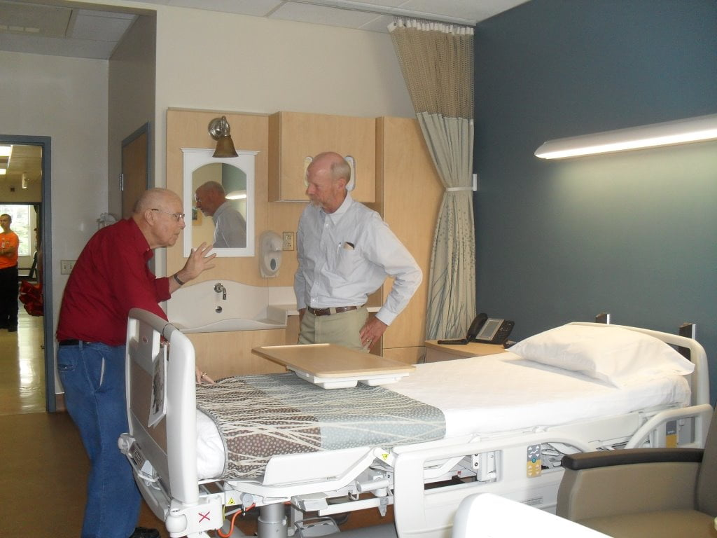 ELMERDILLEY, LEFT, longtime Pocahontas Memorial Hospital employee and cousin of the late Donald W. Pethtal, talks with PMH board president Dr. Bob Must. Dilley had the honor of cutting the ribbon Thursday to open the door to the newly refurbished hospital room. PMH hopes that a successful Capital Campaign will make renovation of all patient rooms a reality. J. Graham photo