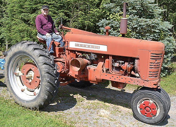 Arbovale resident Artie Barkley sits on one of his 16 Farmall tractors that he has collected over the years. Barkley enjoys tractors which remind him of the days he spent as a young man working on farms in the county. S. Stewart photo