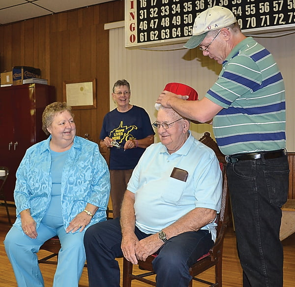 Kess Pritchard, left, smiles as Doug Galford crowns her husband, George, King of Dunmore Daze last Friday evening. Kathy Garber watches and waits to crown Kess as Queen. S. Stewart photo