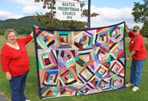 George and Kestra Pritchard, of Dunmore, show off the 2014 Harvest Day quilt, hand-crafted by Baxter Presbyterian Church members and friends. The quilt will be sold at auction during the Harvest Day celebration at the Dunmore Community Center on Saturday, September 27 at 1 p.m. A variety of local items, including jellies, jams, arts and crafts, produce and lotion, also will be offered at the auction. Proceeds will benefit the upkeep of historic Baxter Church.
