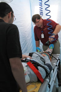 Pocahontas Memorial Hospital employees Michael Stewart and Dean Gunter work inside a mobile, inflatable tent to decontaminate a patient during a  training exercise last Wednesday. The tent can be deployed at hazardous material spill locations to clean patients before transport in an ambulance and prevent contamination of the ambulance fleet.