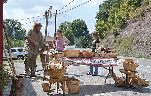 Green Bank residents Luann and Marilyn Creager watch as Virginia crafter, Nathan Jenkins demonstrates wood carving on his spring-pole lathe at the Labor Day event at the Green Bank Gallery Saturday. S. Stewart photo