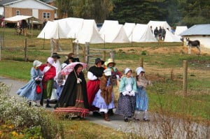 Ladies and girls in period costume walk through the streets of Huntersville during Traditions Day.