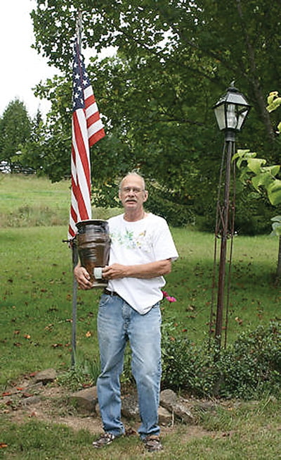 Potter Eric Stahl holds the vase he made at the John C. Campbell Folk Art School in Brasstown, North Carolina. The small cup he is holding in front of the vase was made at his home studio. Photo courtesy of Eric Stahl
