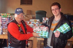 Norris Long, Vice President of the Greenbrier Valley Circuit Riders Chapter of the Christian Motorcyclists Association (CMA), presents donated gifts to Family Resource Network volunteer Max Dunz, on Friday at the FRN Center in Marlinton. The gifts were provided by The Greenbrier and the First Baptist Church of Fairlea, and collected by the CMA during their annual outreach program. Dunz is a tenth grader at Pocahontas County High School. For more information on the CMA, call Long at 304-799-6447.