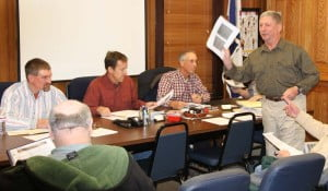 Retired Marine Corps officer Bill McHenry distributes copies of his slideshow briefing during a Pocahontas County Commission meeting on December 2. McHenry presented a briefing on recommended revisions to the state statute authorizing creation of resort area districts (RADs) in West Virginia, and why revisions to the current law are needed before a RAD should be formed at Snowshoe or anywhere in the state.