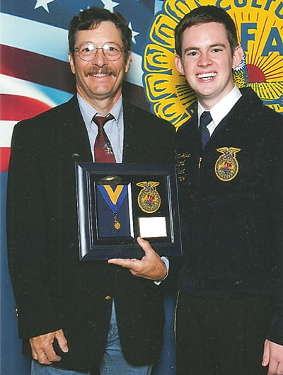 Retired forestry teacher and FFA advisor Mike Burns, left, received the Honorary American FFADegree at the National FFAConference this fall. Presenting the award was National FFAofficer Brian Walsh, of Virginia. Photo courtesy of Mike Burns