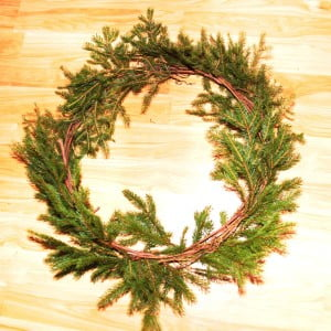 Pine snippets are inserted into the braided coil and secured with wire. At this point, the spruce snippets have been added. Hemlock and white pine snippets will be added next to complete a basic pine wreath.