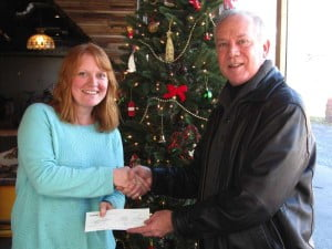 FirstEnergy External Affairs Manager John Norman presents a check for $1,500 to Sarah Irvine, with the Pocahontas Chamber of Commerce. The donation will support the annual Possum Trot 5k Run & Walk, a fundraising event for High Rocks Academy for Girls.