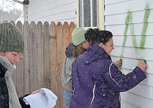 Pretty Penny Café owner Blair Campbell joins community members and friends Joanna Burt-Kinderman, left, and Amy Cimarolli, in removing the racial slur that was spray painted on the restaurant last Wednesday. With a little elbow grease, determination and brake fluid, the words were removed. S. Stewart photo