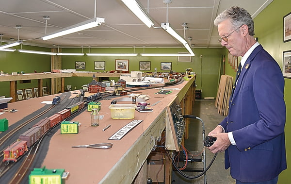 Green Bank resident Bruce Elliott operates a train in his model train exhibit near his home. Elliott decided to have a building put up on his property to house the large exhibit of B&ORailroad trains. As an example of his love of the B&O, Elliott is wearing an authentic B&Oconductor's suit he bought at an auction. S. Stewart photos