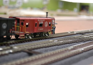 A close up of a caboose shows Elliott's dedication to the smallest of details. A lineman holds on to the caboose as he monitors the train's progress. Buildings, people, animals and vehicles add much to the train display.