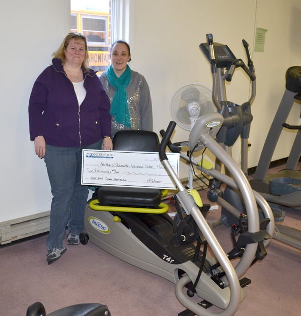 Snowshoe Foundation Executive Director Jessica Stump, left, presents a grant totaling $2,000 to Northern Pocahontas Community Wellness treasurer Malinda Meck. The money was used to purchase the NuStep T4r cross trainer shown in the photo. S. Stewart photo