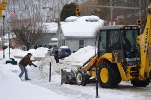 Following a 36-hour weekend snowstorm, Marlinton town workers were hard-pressed to clear mountains of snow from streets. In the photo, Marlinton Maintenance Chief Mike Ryder operates a front-end loader to load snow into dump trucks, while another worker cleans off sidewalks the old-fashioned way.