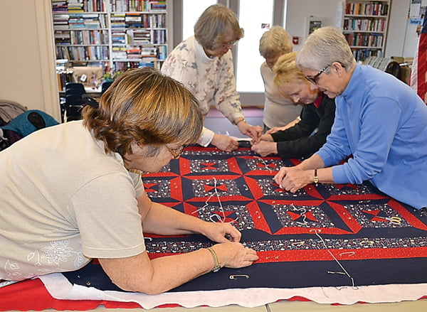 Quilters gather at the Green Bank Library to work on a Ladybug Quilt which will be given to a child or family in need. From left:Kathy Norrod, Mary Ann Alonso, Beth Ruth Crist, Renae Wooddell and Linda Stewart use the knotting technique to sew the quilt together. S. Stewart photo
