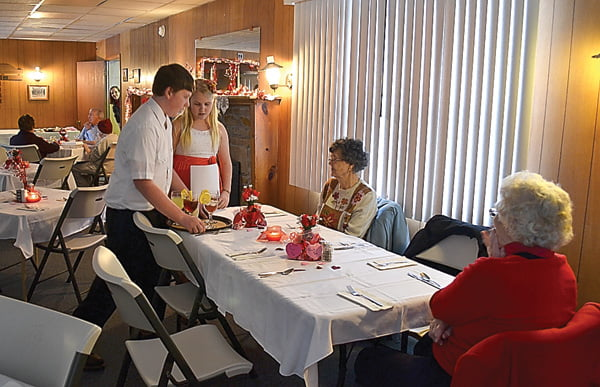Braving the cold weather and snowy road conditions, sweethearts, friends and family gathered at the Arbovale Community Center Saturday to enjoy a Valentine's Day dinner served by the youth groups from New Hope Church of the Brethren. Above, Noah Barkley and Sienna Bircher serve drinks to diners as they await their steak dinners. S. Stewart photo