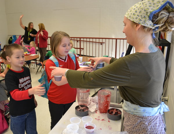 Farm-to-School AmeriCorps Holly Bradley, right, serves fresh smoothies to students at Hillsboro Elementary School Wednesday as part of the Local Foods Day and Fuel Up to Play 60 kick-off celebration. S. Stewart photo