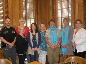 Members of the Pocahontas County Multi-Disciplinary Team, front: l to r: CYAC  Victim's Advocate Barbara Stone;  CYAC Forensic Interviewer JoAnna Willis;  Pocahontas County Schools Counselor Janessa Henderson; Family Refuge Center Advocates Kim Beverage and Selina Gay, wearing teal scarves - the color for Child Abuse Prevention Month; Pocahontas County Schools nurse Jenny Friel. Back row: Pocahontas County Sheriff's Deputy Brandon Kelly and Assistant Prosecuting Attorney Keith McMillion.         J. Graham photo
