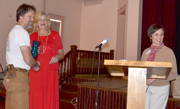 2015 Tourism Person of the Year Tom Moore, left, accepts the award from 2014 TourismPerson of the Year Ruth Taylor. Pocahontas County Convention and Visitors Bureau executive director Cara Rose commended Moore for his vision. S. Stewart photo
