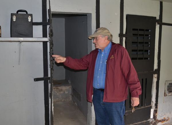Jason Bauserman points out the dents and dings in the cell door of the Durbin Jail as he guides a tour through the building. He said it looks as though prisoners beat on the doors to try to escape or take out their frustration, which left the doors permanently bowed. S. Stewart photo