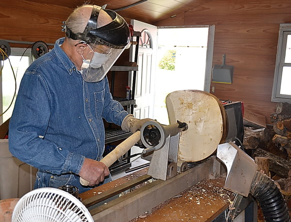 Jim Johnson, of Hillsboro, demonstrates the use of a lathe to chip away at a piece of wood to create a bowl. As the lathe turns, Johnson methodically uses a chisel to make a smooth cut.  S. Stewart photo