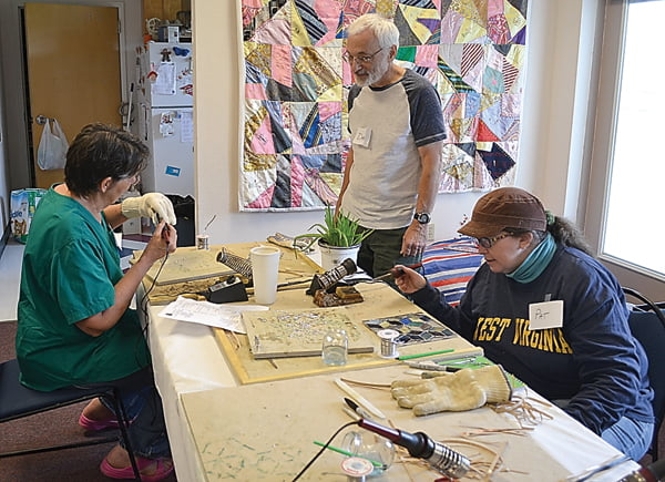 Instructor Dave Houser, center, monitors the progress of students Retta Blankenship, left, and Pat Wilfong, during the stained glass class at Green Bank Public Library Friday. Other participants were Jim Bullard, Kay Beverage, Ann Myers and Suzanne Stewart. S. Stewart photo