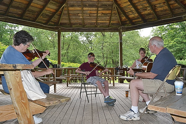"""The beginner and intermediate fiddle class at Allegheny Echoes practiced songs last week at the gazebo at Stillwell Park in Marlinton. From left, Joan Vance, T.D. Sparks and Sarah Riley play """"Old Gray Mare,""""as instructor Danny Arthur accompanies them on guitar. S. Stewart photo"""