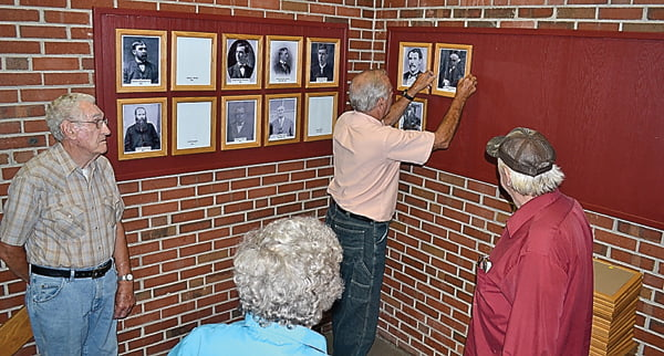 Photographs of all the former mayors of the town of Marlinton were installed in a display at Marlinton Town Hall Thursday. From left, Kenneth Faulknier, Dottie Kellison and Joe Smith watch as Dennis Driscoll hangs one of the photos. The three former mayor's – Kellison, Smith and Driscoll took turns hanging the photos. Faulknier placed his father's, Guy Richard Faulknier – photo. S. Stewart photo