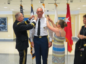 COLONEL JEFFREY PRICE receives his shoulder marks from Army National Guard Lieutenant General Tim Kadavy and Price's daughter, Alexis. Wife, Donna, right, assisted in pinning the silver eagle shoulder marks to her husband's jacket. The  promotion ceremony was held at the Pentagon in Washington, D. C. Photo courtesy of Jeff Price