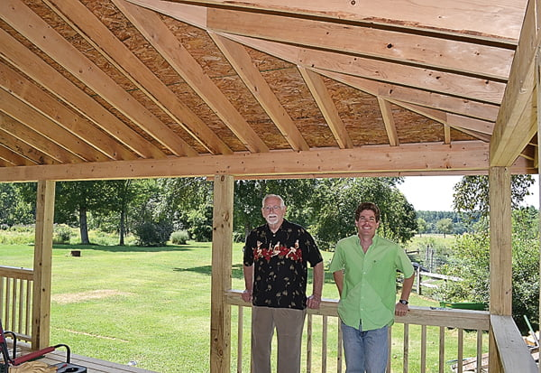 """The artist and the contractor – Ron Radcliff, left, and Ken Jones, stand on the under construction porch at Radcliff's home in Green Bank. Radcliff designed the addition and Jones is """"nailing it."""" S. Stewart photo"""