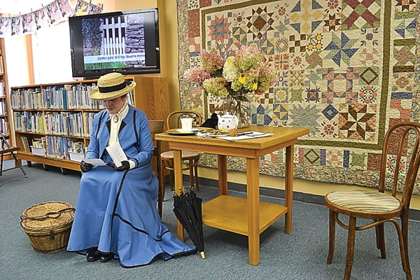 "Beatrix Potter, portrayed by Maria McKelvy, reads a letter as she prepares for her presentation at Hillsboro Library Friday evening. Potter shared memories of her childhood in England and Scotland, and  read ""The Tale of Peter Rabbit,"" her first and most famous book. S. Stewart photo"