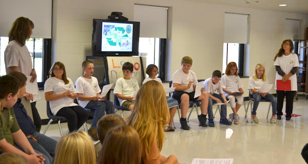 "Students in the ""Legonators"" club at Hillsboro Elementary School give a presentation on a recycling project during the board of education meeting Monday afternoon at the school. From left: second grade teacher Laura Pritt, Allyson Alderman, Robert Pritt, Clayton Burns, Andrea Alderman, Aidan Madison, Logan Hively, Kynlee Wilfong, Jersey Simmons and secretary Sarah Hamilton. S. Stewart photo"