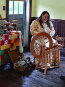 BEAVER CREEK RESIDENT Kim McComb spins wool on the second floor of the Huntersville Schoolhouse during the celebration of historical traditions.